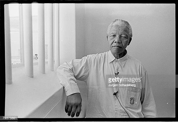 South African president Nelson Mandela revisits his prison cell on Robben Island where he spent eighteen of his twentyseven years in prison 1994