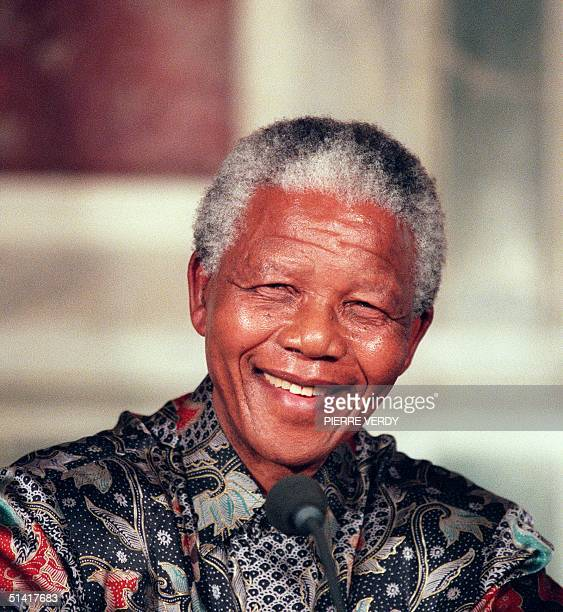 South African President Nelson Mandela smiles 16 July 1966 in Paris as he answers journalists' questions during his official visit to France