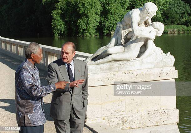 South African President Nelson Mandela speaks with his French counterpart Jacques Chirac 13 July 1996 in the gardens of the Rambouillet's Castle...