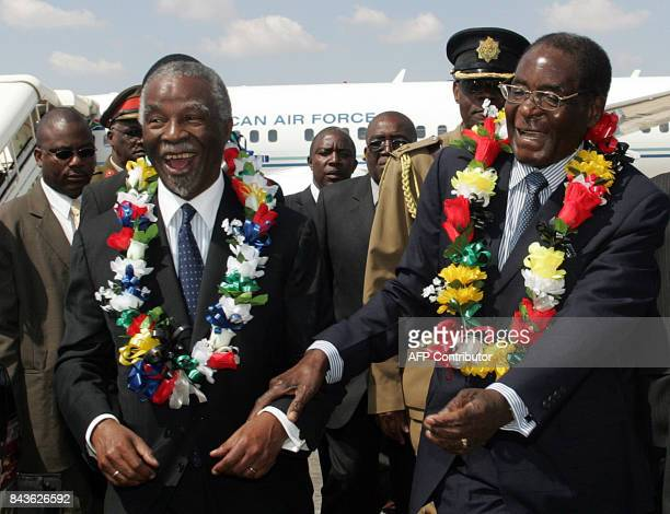 South African President Thabo Mbeki smiles with Zimbabwe President Mugabe at Harare's airport on May 9 2008 Mbeki will interact with the Zimbabwean...