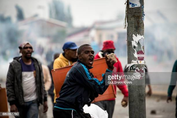 A South African protester throws stones towards riot police in the Eldorado Park district in Johannesburg on May 8 2017 during a demonstration...
