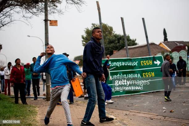 South African protesters throw stones towards riot police in the Eldorado Park district in Johannesburg on May 8 2017 during a demonstration against...