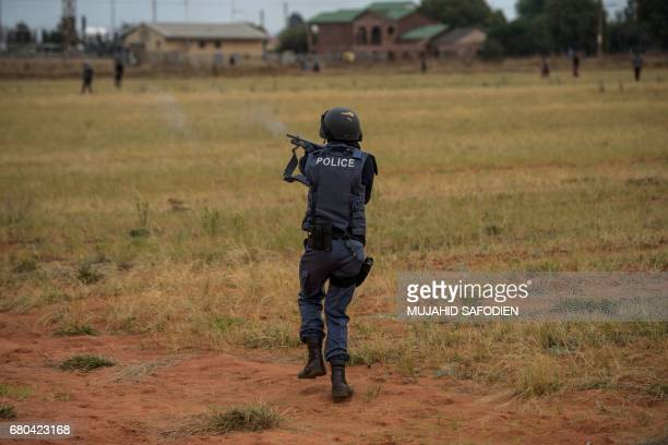 A South African riot police officer shoots rubber bullets in Coligny following clashes that erupted after a court bailed two men accused of killing a...