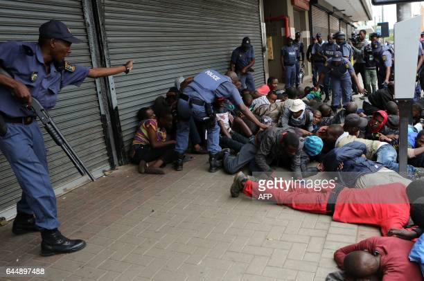 TOPSHOT South African riot policemen detain and arrest South African nationals during a protest march against illegal immigrants on February 24 2017...