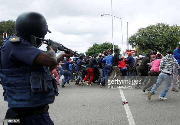 South African riot policemen fire rubber bullets to disperse Somali and foreign nationals clashing with South African nationals during a protest...