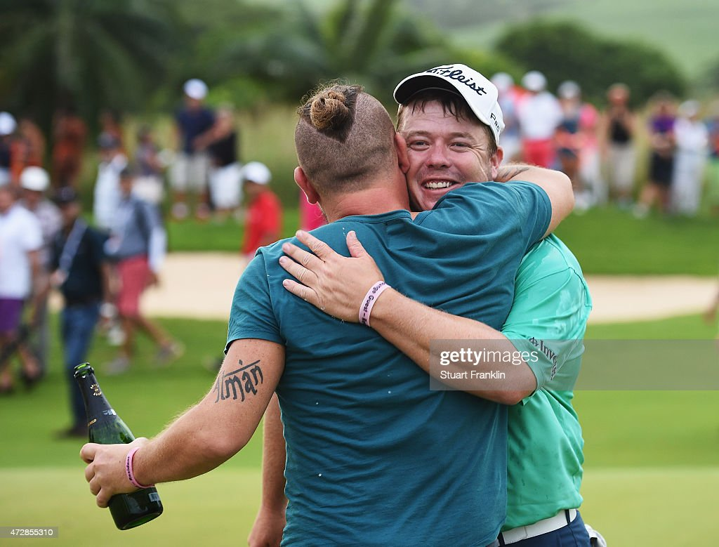 South African rockstar Ard Matthews showers George Coetzee of South Africa with champagne on the 18th hole during the final round of the AfrAsia Bank...