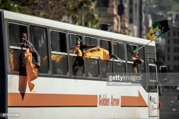 South African ruling party African National Congress and South African President Jacob Zuma supporters hold an ANC flag as they drive in a bus by...