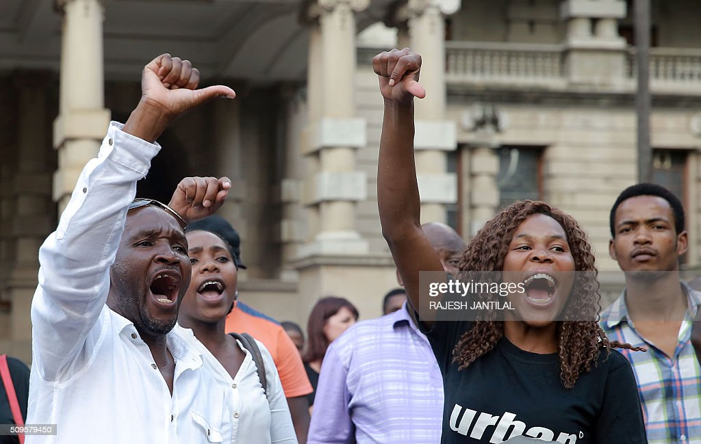 South African ruling party African National Congress President Jacob Zuma supporters argue with #ZUMAMUSTFALL supporters and campaigners demonstrating against South African president Jacob Zuma on February 11, 2016 in Durban, few hours ahead of his annual State of the Nation Address (SONA)at the South African Parliament in Cape Town. Factors fuelling the calls for Zuma to quit include public money spent on his private residence, damage done to the economy when he fired two finance ministers within days, and government corruption. His address to parliament comes just two days after the Constitutional Court heard a crucial case accusing the president of violating his oath to uphold the constitution. JANTILAL