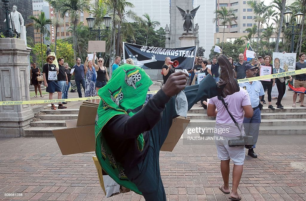A South African ruling party African National Congress (ANC) President Jacob Zuma supporter (R) gestures as he wears a heard scarf picturing the ANC logo in front of #ZUMAMUSTFALL supporters and campaigners demonstrating against South African president Jacob Zuma on February 11, 2016 in Durban, few hours ahead of his annual State of the Nation Address (SONA)at the South African Parliament in Cape Town. Factors fuelling the calls for Zuma to quit include public money spent on his private residence, damage done to the economy when he fired two finance ministers within days, and government corruption. His address to parliament comes just two days after the Constitutional Court heard a crucial case accusing the president of violating his oath to uphold the constitution. JANTILAL