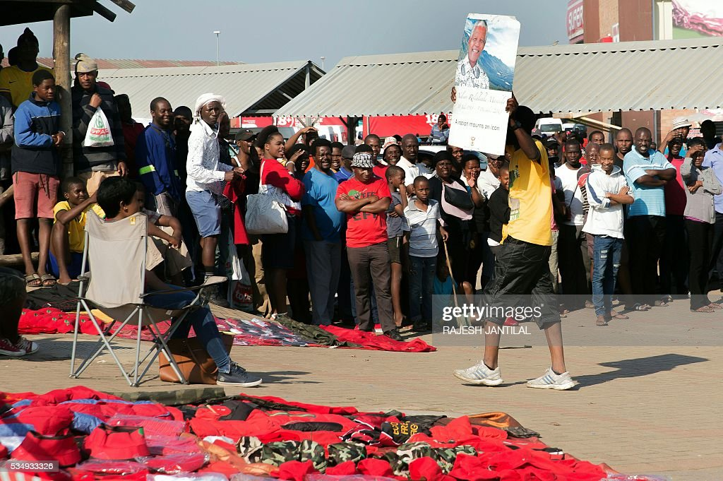 A South African ruling party African National Congress (ANC) supporter walks with a portrait of the late President Nelson Mandela in the middle of South African opposition radical leftist party Economic Freedom Fighters (EFF) members during an official local election campaign launch at the Esikhawini Shopping Centre on May 28, 2016 south of Durban. Malema and his supporters were attacked by a group of African National Congress (ANC) supporters who hurled stones ans rocks as Malema took to the podium. The South African Police Services ( SAPS) fired rubber bullets at the ANC supporters. / AFP / RAJESH