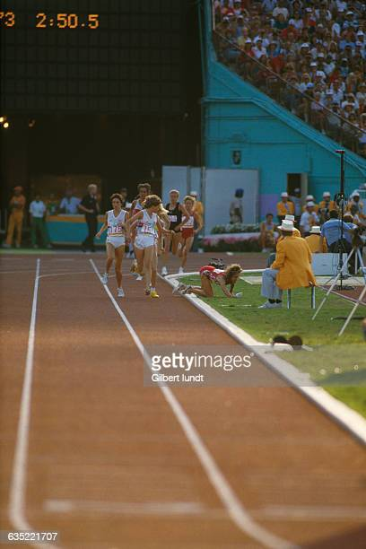 South African runner Zola Budd watches her chief competitor American Mary Decker fall to the ground in the final of the Women's 3000meter run at the...