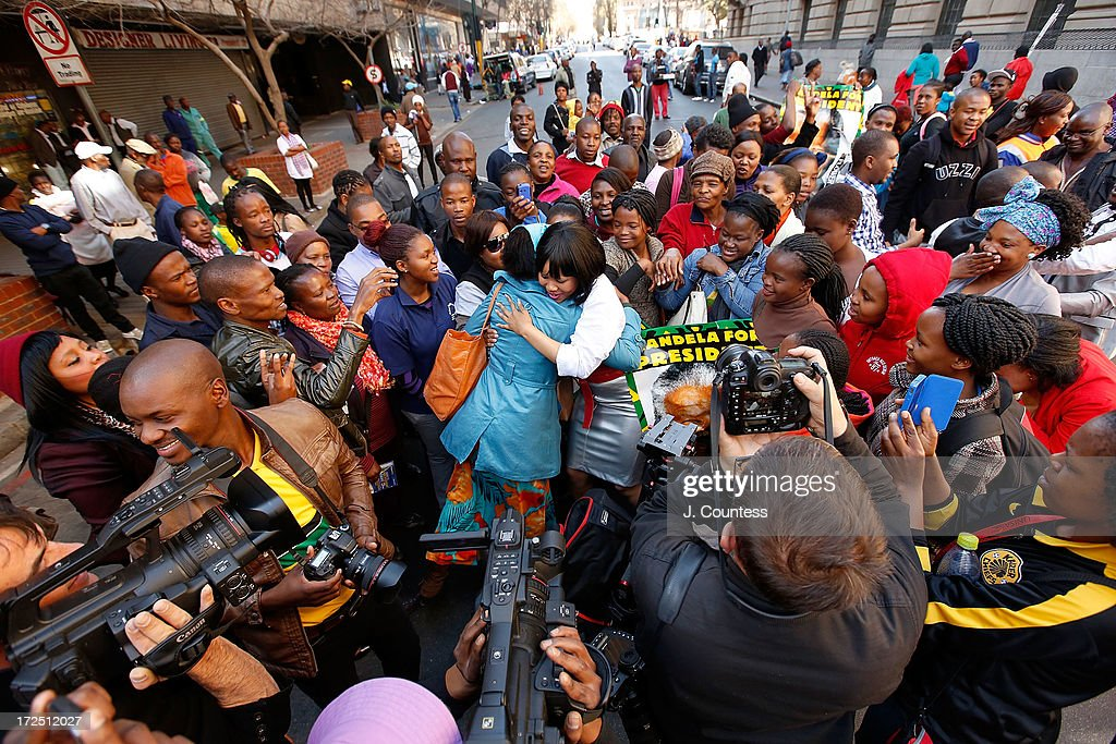 South African singer Chomme (C) hugs a well wisher as people are gathered in support for former South African President Nelson Mandela during an African National Congress-sponsered prayer rally outside ANC headquarters on July 2, 2013 in Johannesburg, South Africa. The anti-apartheid icon and Nobel Peace Prize Laurete has been in the hospital for more than three weeks being treated for a recurring lung infection.