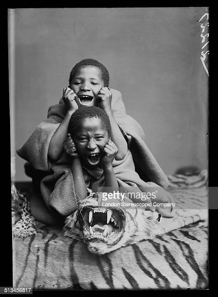 South African singers Albert Jonas and John Xiniwe of The African Choir imitating the roar suggested by a tiger skin rug 1891 The choir drawn from...