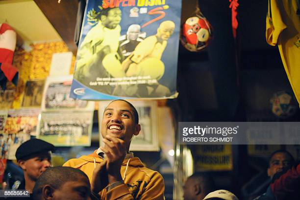 A South African soccer fan and patron of The Place pub and grill claps in delight as he watches the South African soccer team play their semifinals...