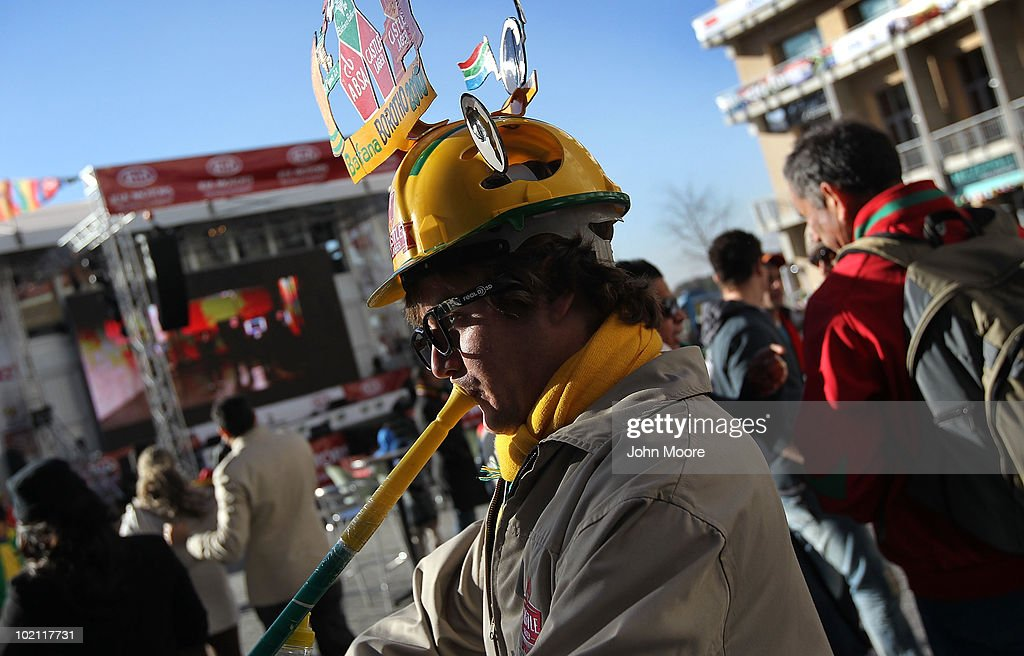 South African soccer fan Ricky Robinson blows into a vuvuzela horn while watching a World Cup match on a large monitor at a public viewing area on June 15, 2010 in Johannesburg, South Africa. Despite freezing temperatures fans came out to watch the matches.