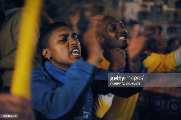 South African soccer fans and patrons of The Place pub and grill react as they watch the South African soccer team play their semifinals match...