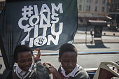 South African students from Chief Albert Luthuli Primary and High School in Daveyton hold a flag reading 'I am constitution' as they take a ride on a...