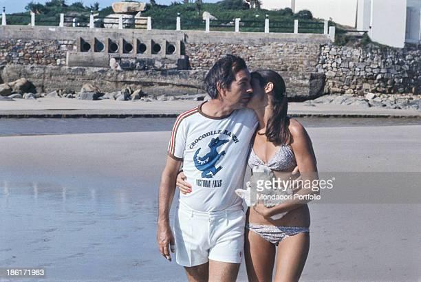 South African surgeon Christiaan Barnard hugging his wife Barbara Zoellner by the sea Plettenberg Bay 1977