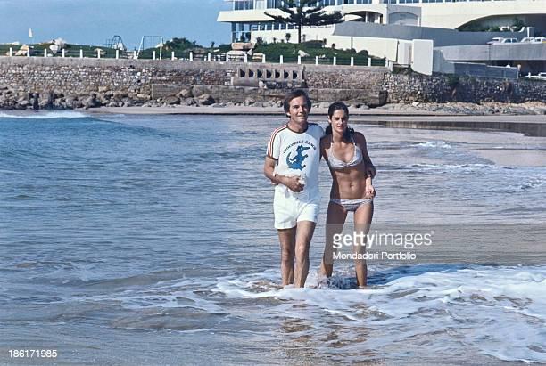 South African surgeon Christiaan Barnard walking hugging his wife Barbara Zoellner by the sea Plettenberg Bay 1977