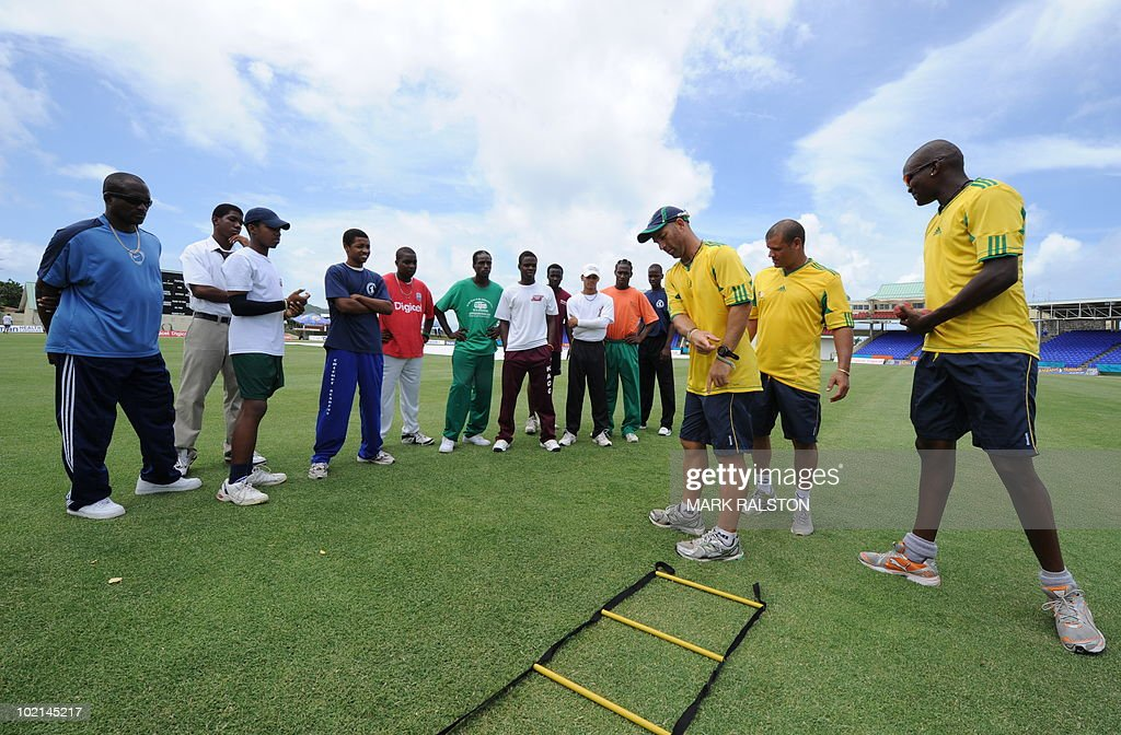 South African trainer Robert Walter (C) batsman Ashwell Prince (2nd R) and bowler Lonwabo Tsotsobe (R) during a training clinic for members of the St. Kitts Junior Cricket Academy team, before the second test at the Warner Park ground in the St Kitts capital of Basseterre on June 16, 2010. South Africa have taken a 1-0 lead in the three-Test series, with the second test beginning on June 18. AFP PHOTO/Mark RALSTON
