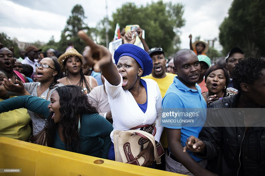 A South African woman reacts at the news that the time is over to visit the remains of former South African President Nelson Mandela at the Union Buildings on December 12, 2013 in Pretoria. Nelson Mandela was reclaimed by ordinary South Africans who queued in huge numbers in the hot sun Thursday to file past his open casket on a day reserved for the public. Mandela, the revered icon of the anti-apartheid struggle in South Africa and one of the towering political figures of the 20th century, died in Johannesburg on December 5 at age 95. AFP PHOTO / MARCO LONGARI