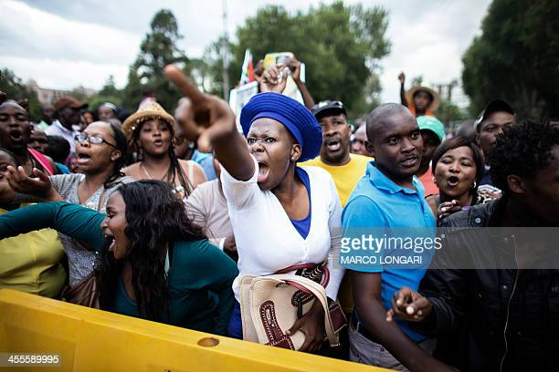 A South African woman reacts at the news that the time is over to visit the remains of former South African President Nelson Mandela at the Union...