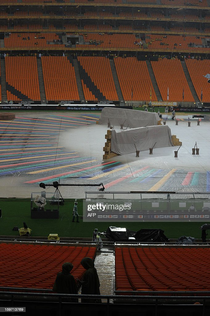 South African workers in the rain try and set up for opening ceremonies of 2013 Africa Cup of Nations at Soccer City stadium in Soweto on January 19, 2013 .