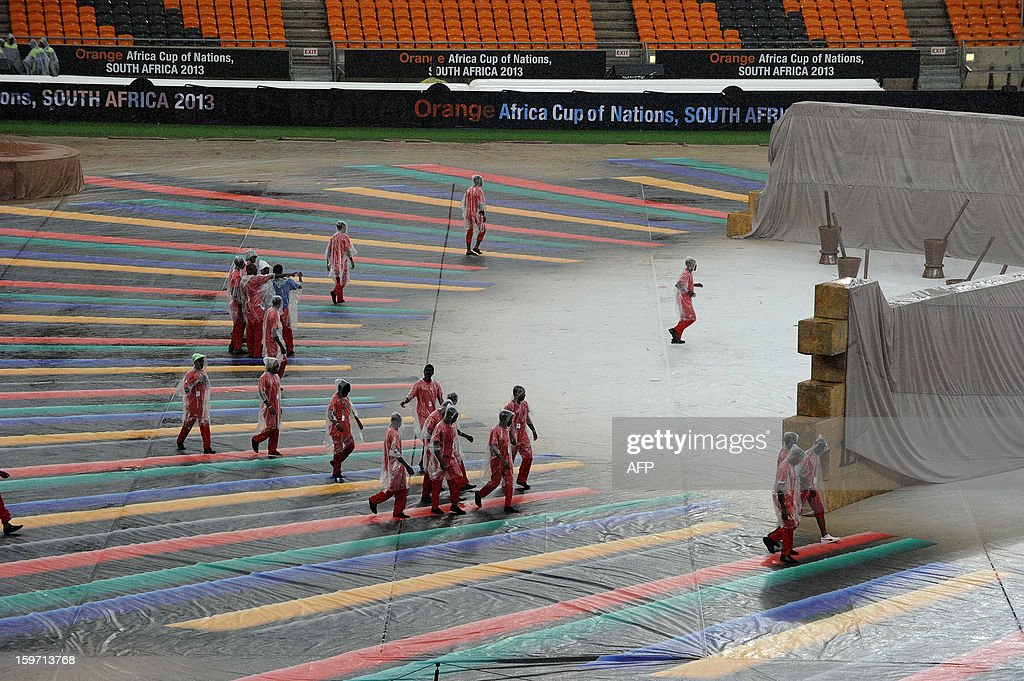 South African workers in the rain try and set up for opening ceremonies of the 2013 Africa Cup of Nations at Soccer City stadium in Soweto on January 19, 2013 .
