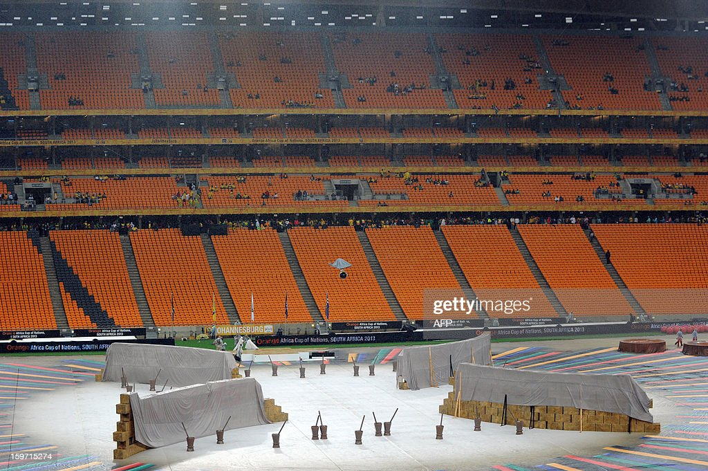 South African workers in the rain try and set up for opening ceremonies of the 2013 Africa Cup of Nations at Soccer City stadium in Soweto on January 19, 2013 . AFP PHOTO / ALEXANDER JOE