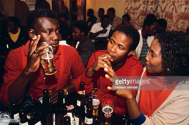 South African yuppies sit and chat and drink beer at a shebeen an unlicensed drinking establishment in Soweto