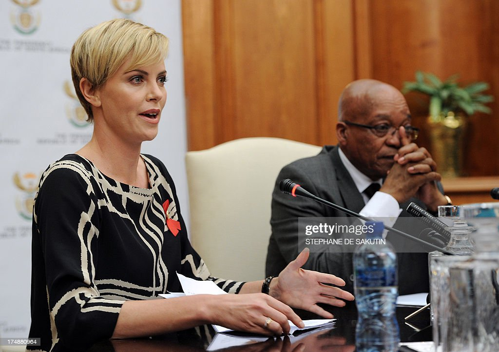 South African-born Hollywood actress and UN Messenger of Peace Charlize Theron speaks during a press conference, alongside South Africa President Jacob Zuma (R), on July 29, 2013, at the Unions Building in Pretoria. Theron is accompanied by the Executive Director of UNAIDS Michel Sidibe to discuss the strides being made in the fight against HIV and AIDS and how collaboration can assist mitigate the pandemic's negative impact on young girls. They will also explore ways to support South Africa's efforts to enable young women and girls to lead healthier HIV and AIDS-free lives.