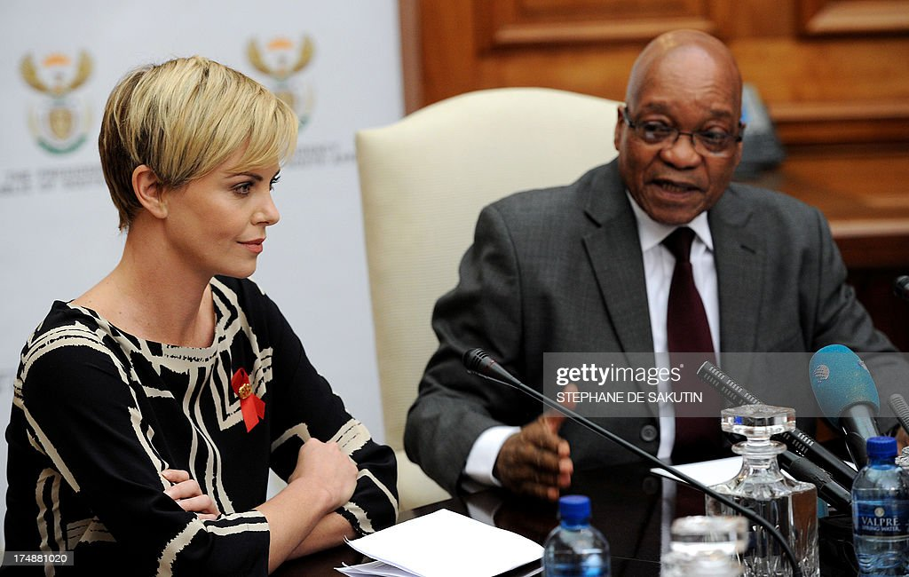 South African-born Hollywood actress and UN Messenger of Peace Charlize Theron attends a press conference, alongside South Africa President Jacob Zuma (R), on July 29, 2013, at the Unions Building in Pretoria. Theron is accompanied by the Executive Director of UNAIDS Michel Sidibe to discuss the strides being made in the fight against HIV and AIDS and how collaboration can assist mitigate the pandemic's negative impact on young girls. They will also explore ways to support South Africa's efforts to enable young women and girls to lead healthier HIV and AIDS-free lives. AFP PHOTO / STEPHANE DE SAKUTIN