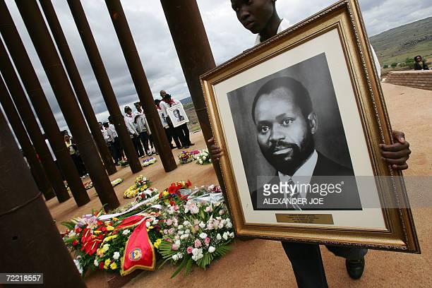 South Africans hold a photo of late President Samora Machel and other victims of his plane crash 19 October 2006 in Mbuzni at a memorial built on a...