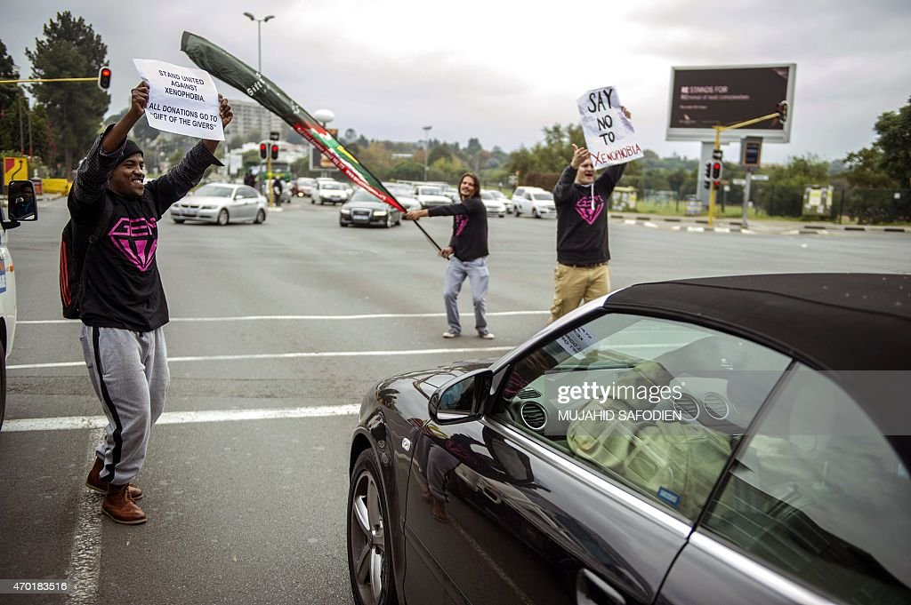 South Africans hold up signs on the side of the road in Sandton an affluent area of Johannesburg as they try to make people more aware of the...