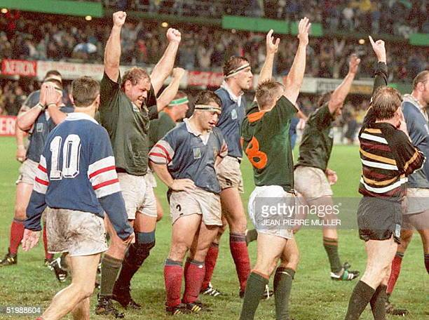 South Africans Pieter Du Randt and Johan Roux celebrate their victory over France as French hooker JeanMichel Gonzalez hangs his head as the referee...