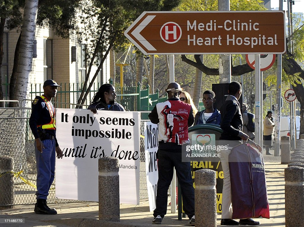 South Africans prepare to put up signs quoting (L) and wishing well (R, obscured) former South African president Nelson Mandela on June 25, 2013 outside of the Mediclinic heart hospital in Pretoria where Mandela is receiving treatment. Mandela's close family gathered today at his rural homestead to discuss the failing health of the South African anti-apartheid icon who was fighting for his life in hospital. Messages of support poured in from around the world for the Nobel Peace Prize winner, who spent 27 years behind bars for his struggle under white minority rule and went on to become South Africa's first black president. AFP PHOTO / ALEXANDER JOE