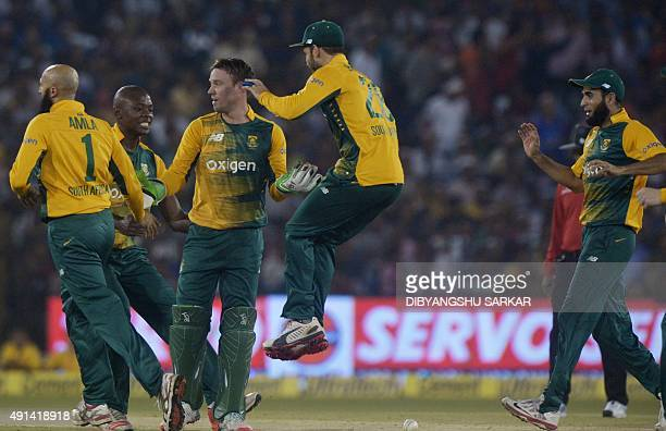 South Africa's AB de Villiers celebrates with teammates after running out India's Virat Kohli during the second T20 cricket match between India and...