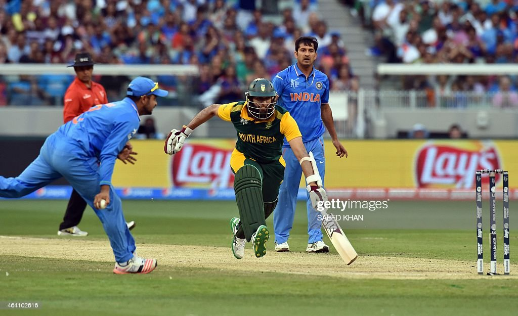 South Africa's batsman Hashim Amla rushes to gain his ground as India's fielder Suresh Raina fails to hit the stumps during the Pool B 2015 Cricket...