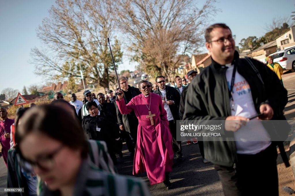 TOPSHOT South Africa's Bishop Malusi Mpumlwana leads a peace walk in Soweto on June 11 2016 to commemorate the 40th anniversary of the Soweto...