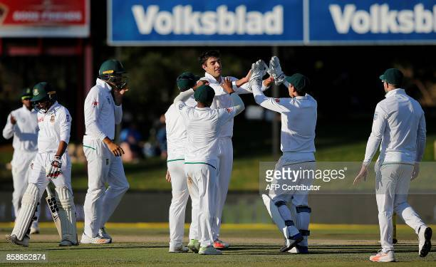 South Africa's bowler Duanne Olivier is congratulated by teammates after his dismissal of Bangladesh's batsman Taijul Islam during the second day of...