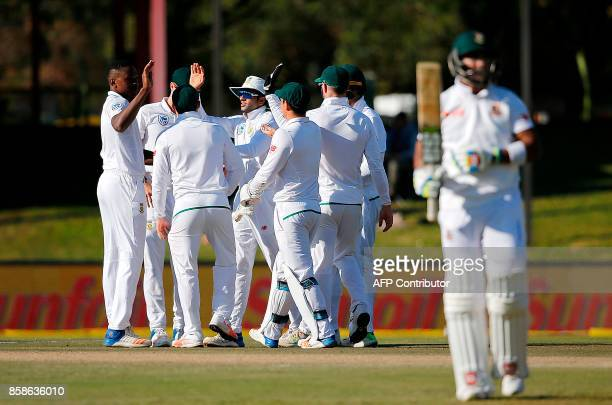 South Africa's bowler Kagiso Rabada is congratulated by teammates after his dismissal of Bangladesh's batsman Sabbir Rahman during the second day of...