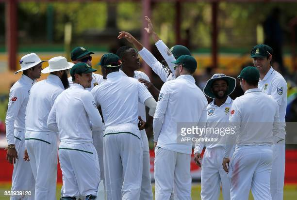 South Africa's bowler Kagiso Rabada is congratulated by teammates after taking his 100th Test match wicket during the third day of the second Test...