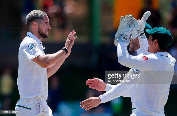 South Africa's bowler Wayne Parnell celebrates with teammates after the dismissal of Bangladesh's batsman Mushfiqur Rahim during the third day of the...