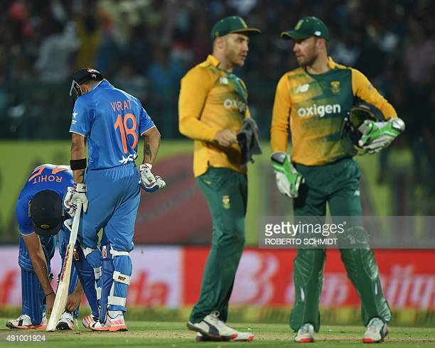 South Africa's captain Faf du Plessis and wicketkeeper AB de Villiers chat as India's Virat Kohli and India's Rohit Sharma speak during the first T20...