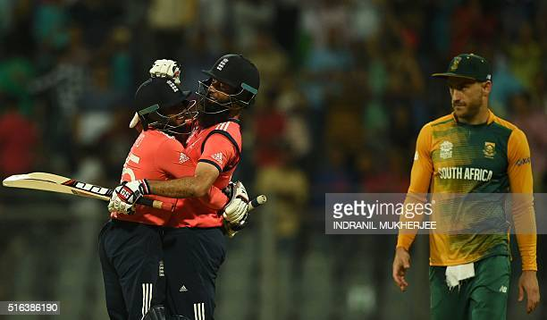 South Africa's captain Faf du Plessis looks on as England's Adil Rashid and Moeen Ali celebrate after winning the World T20 cricket tournament match...
