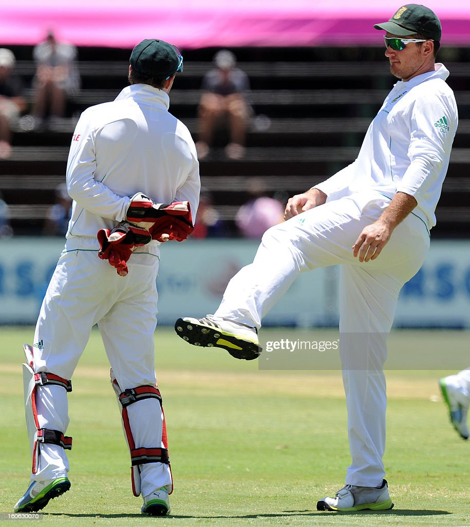 South Africa's captain Greame Smith (R) congratulates AB de Villiers with a kick in the back side for a record breaking of a wicket keeper to take most south african catches in one test match during day four of the first Test match between South Africa and Pakistan at Wanderers Stadium in Johannesburg on February 4, 2013. AFP PHOTO / Stringer1