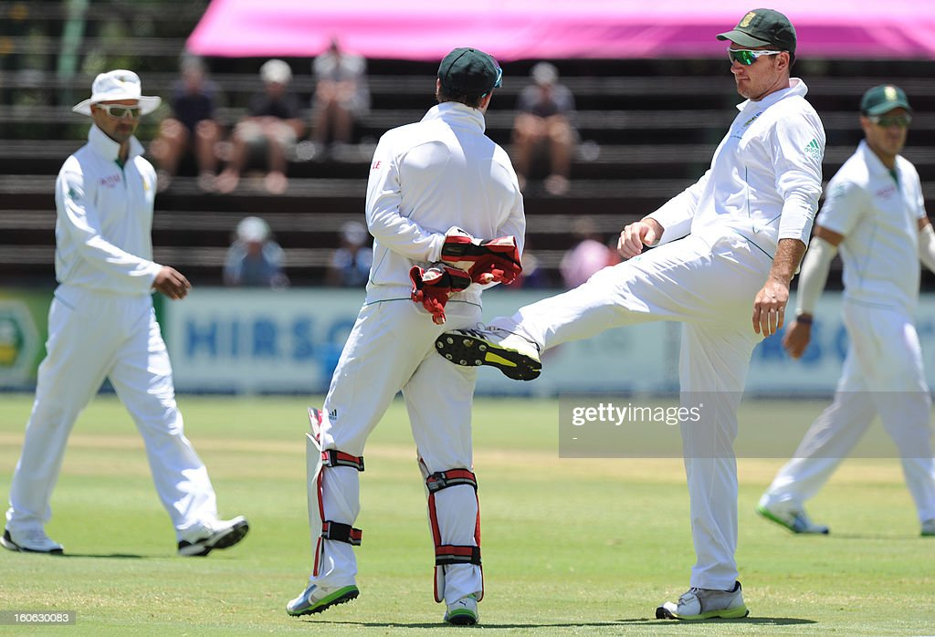 South Africa's captain Greame Smith (R) congratulates AB de Villiers with a kick in the back side for a record breaking of a wicket keeper to take most south african catches in one test match during day four of the first Test match between South Africa and Pakistan at Wanderers Stadium in Johannesburg on February 4, 2013.
