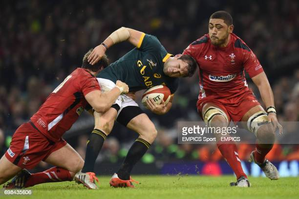 South Africa's Cobus Reinach is tackled by Wales' Dan Biggar and Taulupe Faletau
