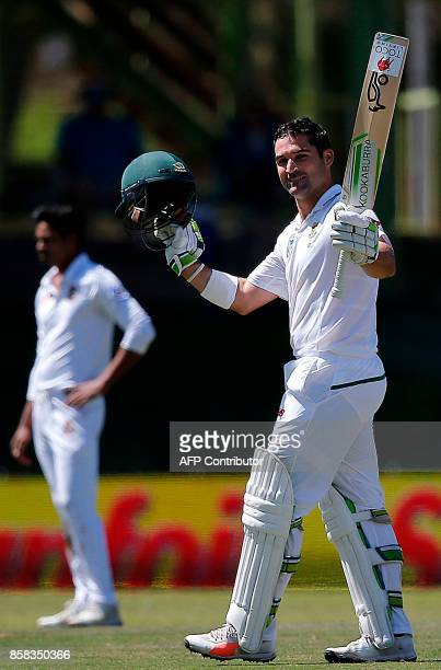South Africa's Dean Elgar raises his bat as he celebrates after scoring a century during the first day of the second Test cricket match between South...