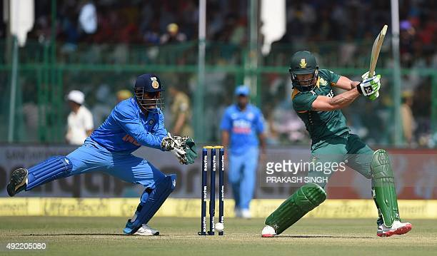 South Africa's Faf du Plessis plays a shot as India's captain Mahendra Singh Dhoni looks on during the first one day international cricket match...